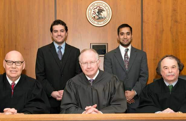 The 2014 Moot Court champion team of second-year law students (standing from left) Nick Perrone and Jesse Guth argued before the distinguished bench of (seated from left): Judge James F. Holderman, United States District Court, Northern District of Illinois; Justice Thomas L. Kilbride, Illinois Supreme Court; and Professor Barry Sullivan, Cooney & Conway Chair in Advocacy and Professor of Law, Loyola University School of Law.