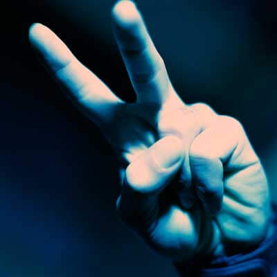 """Photo of a hand with two fingers making the """"peace"""" sign"""