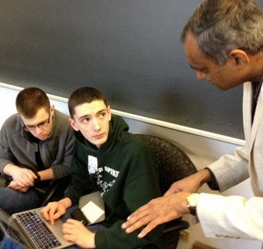NIU Professor Dhiman Chakraborty (rights) talks with students Matthew Williams  (left) and Chase Pipes.