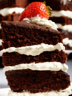 Photo of layered chocolate cake with white frosting and a strawberry on top