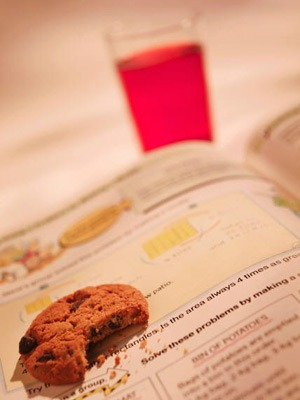 Photo of a half-eaten cookie and a glass of juice with an open textbook