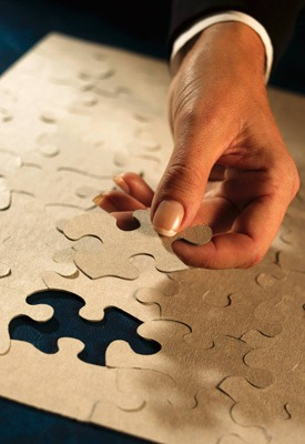 Photo of a hand putting in the final piece of a jigsaw puzzle