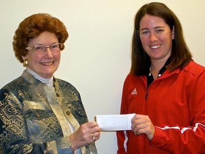 Sally Stevens (left) presents a check to Kim Kester.