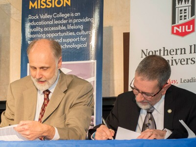 Presidents Doug Baker and Mike Mastroianni sign an agreement to allow students to apply NIU credits towards an RVC associate's degree.