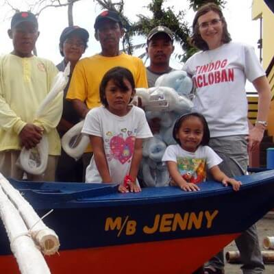 "Katharine Wiegele poses in Tacloban City with boat recipient and fisherman Rodrigo Enico (far left) and his family during the boat blessing and handover in Tacloban City. Enico's motorboat was named after DeKalb resident and donor Jennifer Mescher, childhood friend of Wiegele. Enico's livelihood has always been fishing but until now he did not have a boat of his own. ""It took Typhoon Haiyan for me to have my own boat,"" he said."
