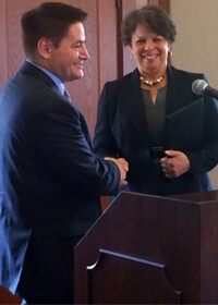 Sharon Banks-Wilkins shakes hands with board chair John Butler following his reading of a resolution in her honor.