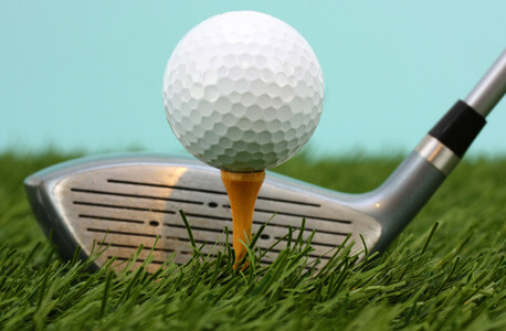 Photo of golf ball on tee and club