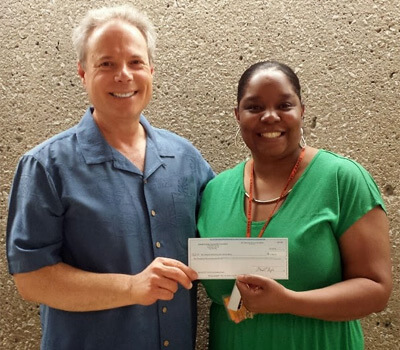 Dean Rich Holly receives the grant check from Latricia Dawkins, board member of the DeKalb County Community Foundation.