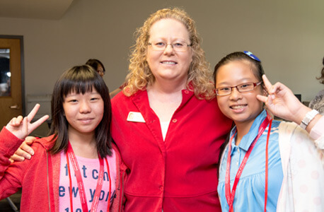 Gail Hayenga, conference and event coordinator in the NIU College of Education's Office of External & Global Programs, greets two American Summer Education Camp students from the National University of Tainan Affiliated Elementary School.