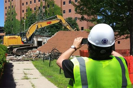 Alex Gelman, director of the NIU School of Theatre and Dance, photographs work to demolish the Stevens Building.