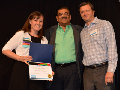 NIU's Randi Napientek is congratulated by Mahendran Jawaharlal (center) and Sean Sullivan of EBI MAP-Works.