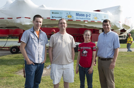 Mike McEvoy, Aaron Epps, Mary Shenk and Professor Mike Eads stand in front of the Muon g-2 magnet during the July 26 move.