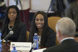 Angela Isom (left) looks on as Aysha Flowers tells her student loan story to Senator Dick Durbin.