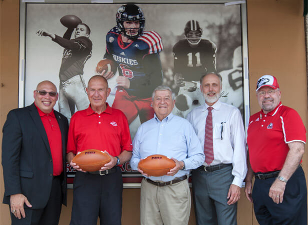 For the second consecutive fall, NIU and the City of DeKalb have partnered to display window clings at DeKalb businesses featuring the NIU football program. From left: NIU Associate Vice President/Director of Athletics Sean Frazier, Huskie football legends George Bork and Bob Heimerdinger, NIU President Doug Baker and DeKalb Mayor John Rey unveil the first of the new clings July 22 at the Lincoln Inn in downtown DeKalb.