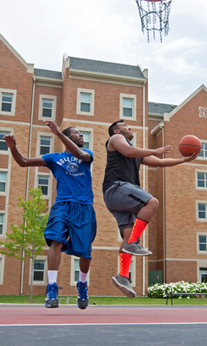 Students play basketball outside New Hall.