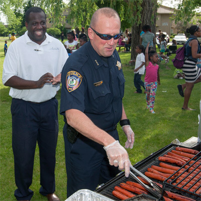 A City of DeKalb police officer grills hot dogs at the Camp Power barbecue.