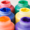 A photo of six jars of colorful paint