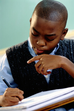 Photo of an African-American boy taking notes in class
