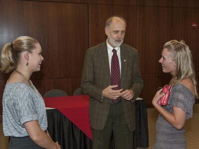NIU President Doug Baker talks to new transfer students Alexis Massman and Lisa Matson
