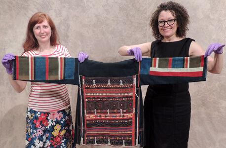 Lisa Callahan and Patty Kirk from Moxie display a traditional Akah woman's jacket from Laos.
