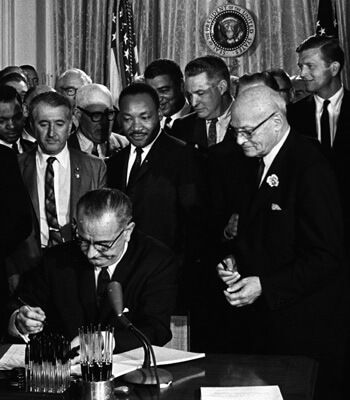 President Lyndon B. Johnson signs the 1964 Civil Rights Act as Martin Luther King Jr. and others look on. Cecil Stoughton, White House Press Office