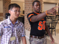 A DeKalb High School student shows a visitor from Taiwan around the school.