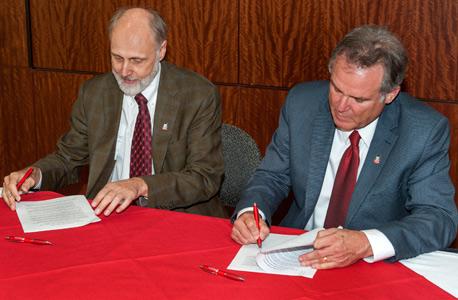 NIU President Doug Baker (left) and College of Lake County President Girard W. Weber sign an innovative reverse transfer agreement.