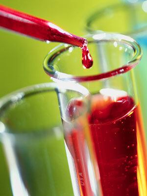 Photo of a red liquid being dropped into a beaker