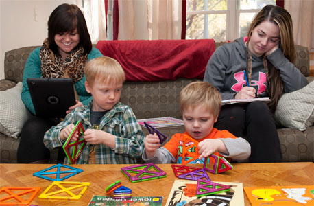 Student-parents Destiny Engels (left) and Heather Theissing study in the Campus Child Care North Corner Room while their sons, Randal and Jeremiah, play.
