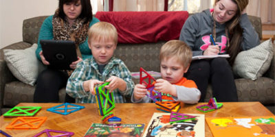 Student-parents Destiny Engels (left) and Heather Theissing study in the North Corner Room of Campus Child Care while their sons, Randal and Jeremiah, play.