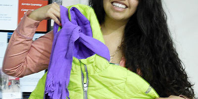 Photo of a Huskie Service Scholar holding a coat and scarf
