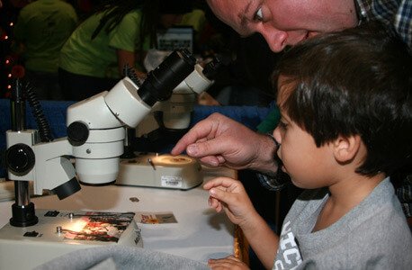 A boy looks into a microscope