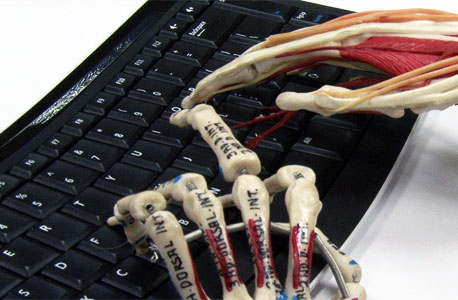 Photo of plastic skeleton fingers typing on a computer keyboard