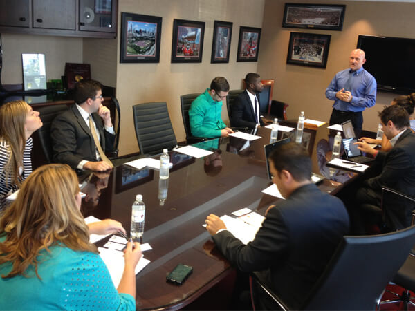 Program director Rod Caughron (standing) discusses the state of program with advisory board members during a United Center meeting.