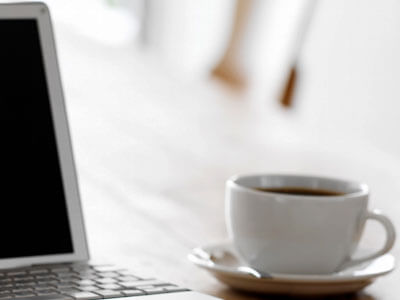 Photo of a cup of coffee and a laptop