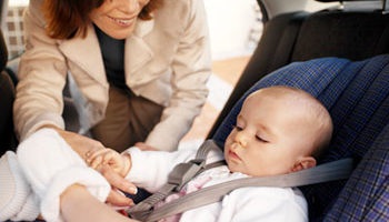 Photo of a working mother buckling her baby in the infant car seat