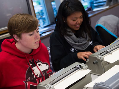 NIU students work with Braille typewriters.
