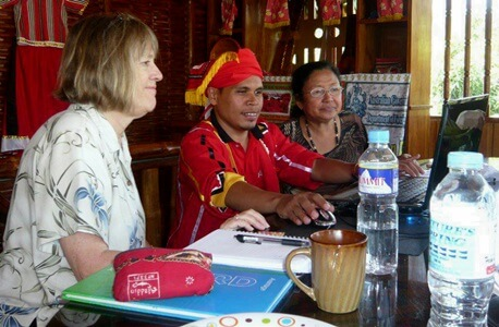 Susan Russell works with an indigenous leader of the Higaonan people in northern Mindanano, Philippines during a previous trip. Historian Noemi Medina is also pictured.