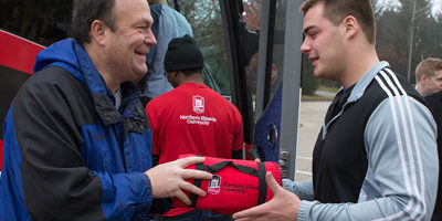 Robert M. Peterson, associate professor and White Lodging Professor of Sales at NIU, hands out NIU fleeces to students boarding the #NIUSalesBus.