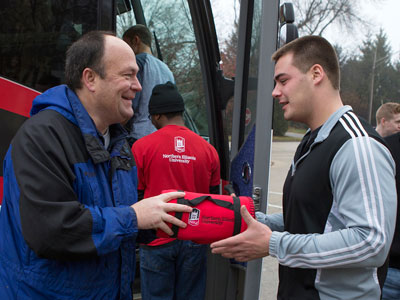 Robert M. Peterson, associate professor and White Lodging Professor of Sales, hands out NIU fleeces to students boarding the #NIUSalesBus.