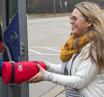 NIU marketing student Martina McNulty gets an NIU fleece as she boards the #NIUSalesBus for a week-long tour of Midwest business centers.