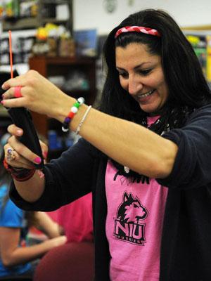 Pettee Guerrero, NIU STEM Outreach associate, loads a hand-held 3D printer pen called a Doodler for a student in the new STEM Divas program.
