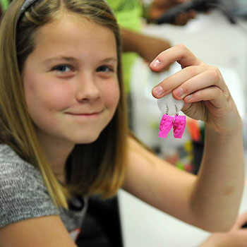 3-D printed earrings, proudly displayed here by a STEM Divas participant, are just one of the projects girls have an opportunity to explore in the program.