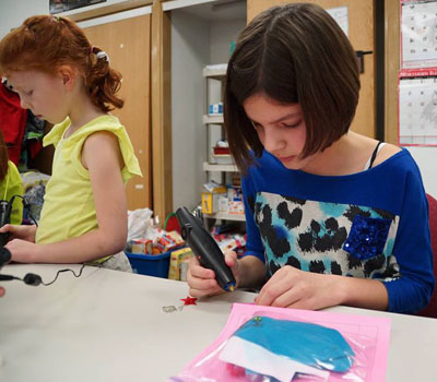 A student in one of the very first STEM Divas classes, held on campus at Northern Illinois University and facilitated by STEM Outreach, works with her Doodler 3D printer pen to create 3-dimensional jewelry.