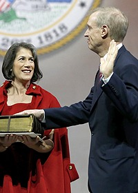 Illinois Gov.-elect Bruce Rauner takes the oath of office from Illinois District Judge Sharon Johnson Coleman as his wife, Diana Rauner, holds a Bible.