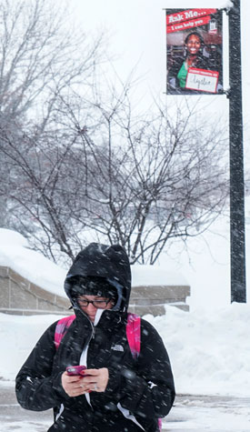 An NIU student checks her cell phone in the snow.