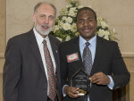 Anthony Roberts displays his award with President Baker