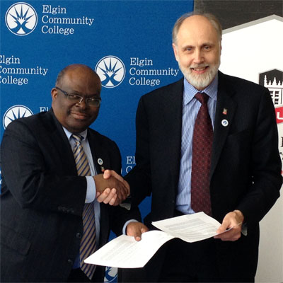 ECC President David Sam shakes the hand of NIU President Doug Baker following the ceremonial signing.