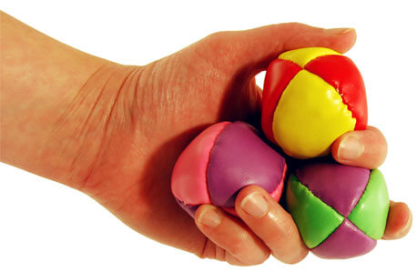 Photo of a hand holding three balls to juggle