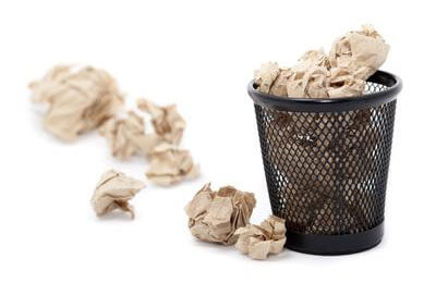 Photo of a trash basket and crumpled-up paper